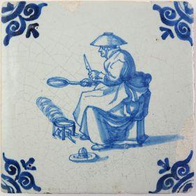 Antique Delft tile with a woman baking pancakes, 17th century