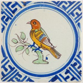 Antique Delft tile with a polychrome bird in Wanli inspired corner motifs, 17th century