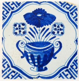 Antique Delft tile with a large flower pot in blue and Wanli inspired corner motifs, 17th century