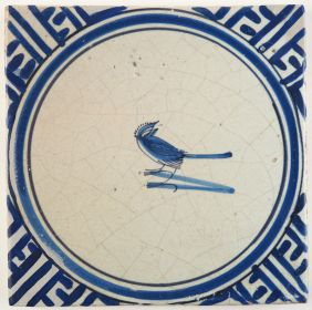 Antique Delft tile in blue with a bird depicted in a circle and Wanli inspired corner motifs, 17th century