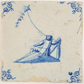 Antique Delft tile in blue with a man laying in the grass while his kite flies up in the air, 17th century